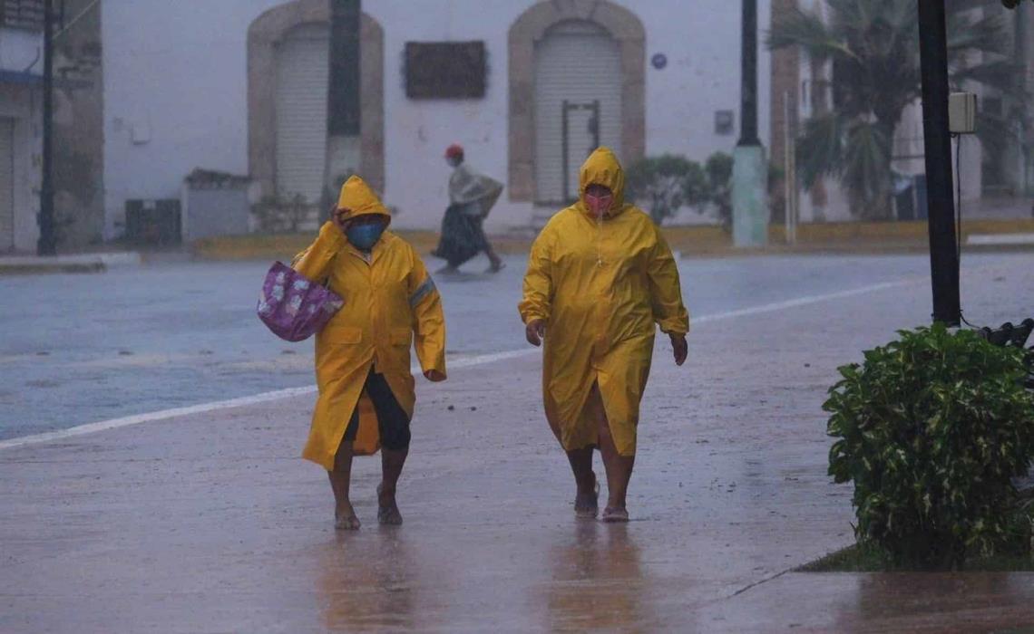 Dos personas protegidas con capas caminan en medio de un fuerte aguacero hoy, en Tizimin, Yucatán. EFE/ Cuauhtemoc Moreno